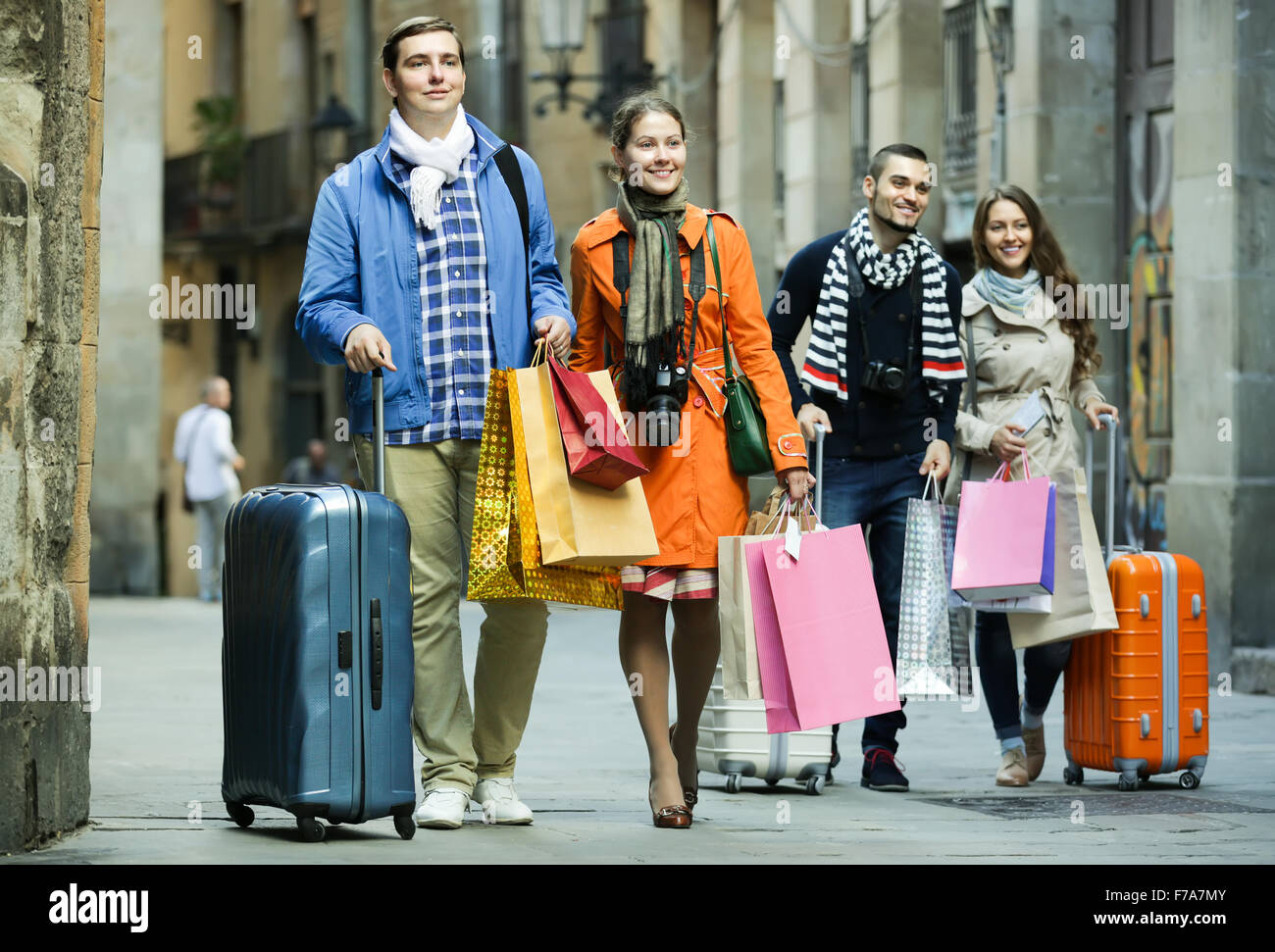Two smiling couples of young tourists with shopping bags and ...