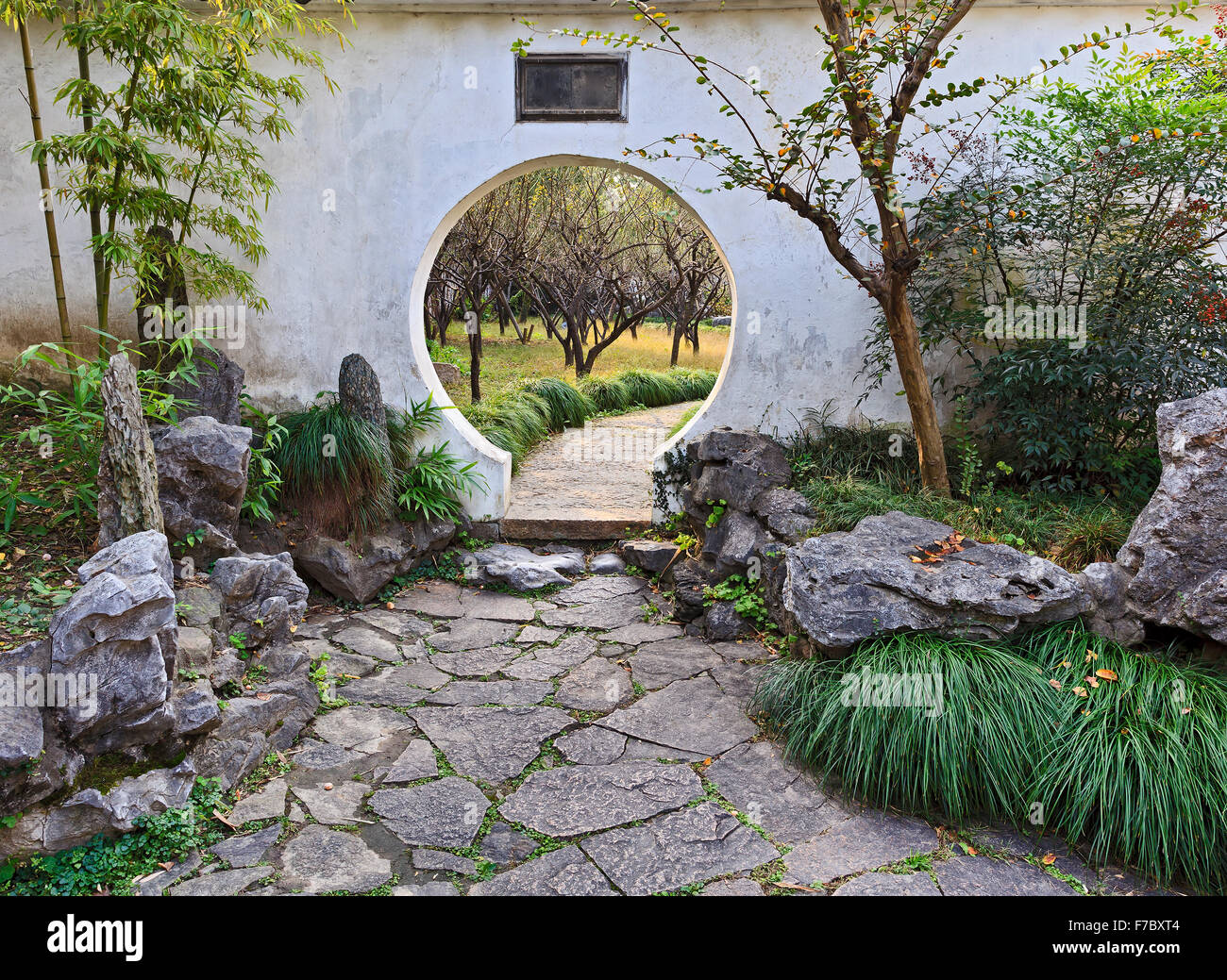 Chinese Formal Traditional Garden White Wall With Round Gate Hole From  Bamboo And Decorative Stones To