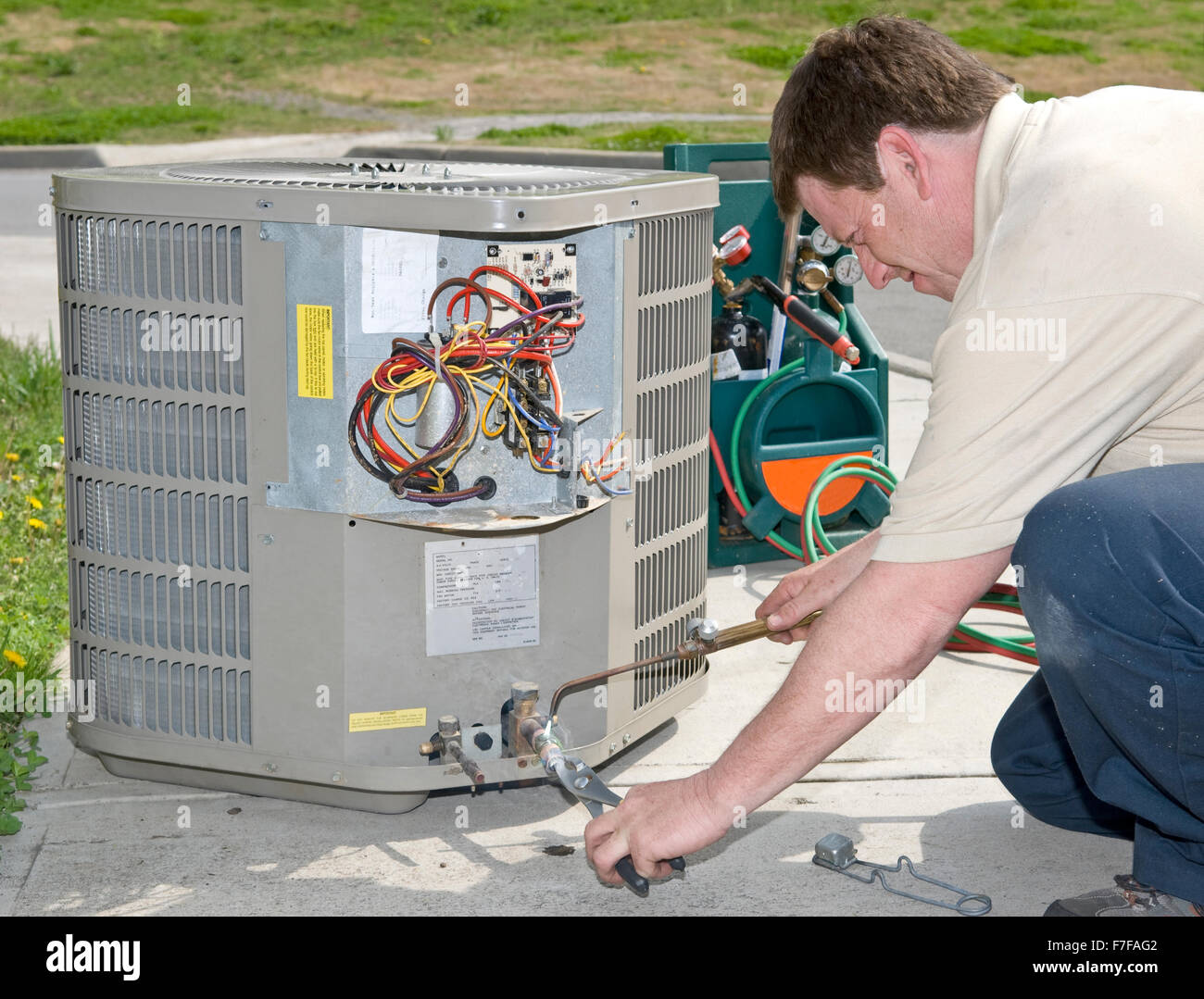ac repairman welds connector on replacement air conditioning unit