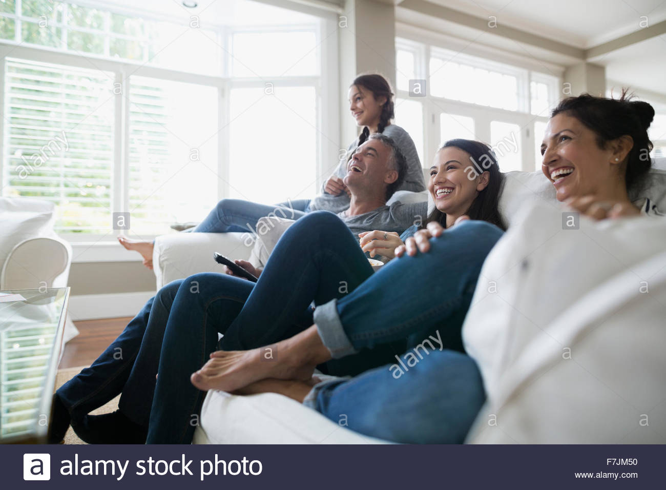 Family Laughing Watching TV On Living Room Sofa