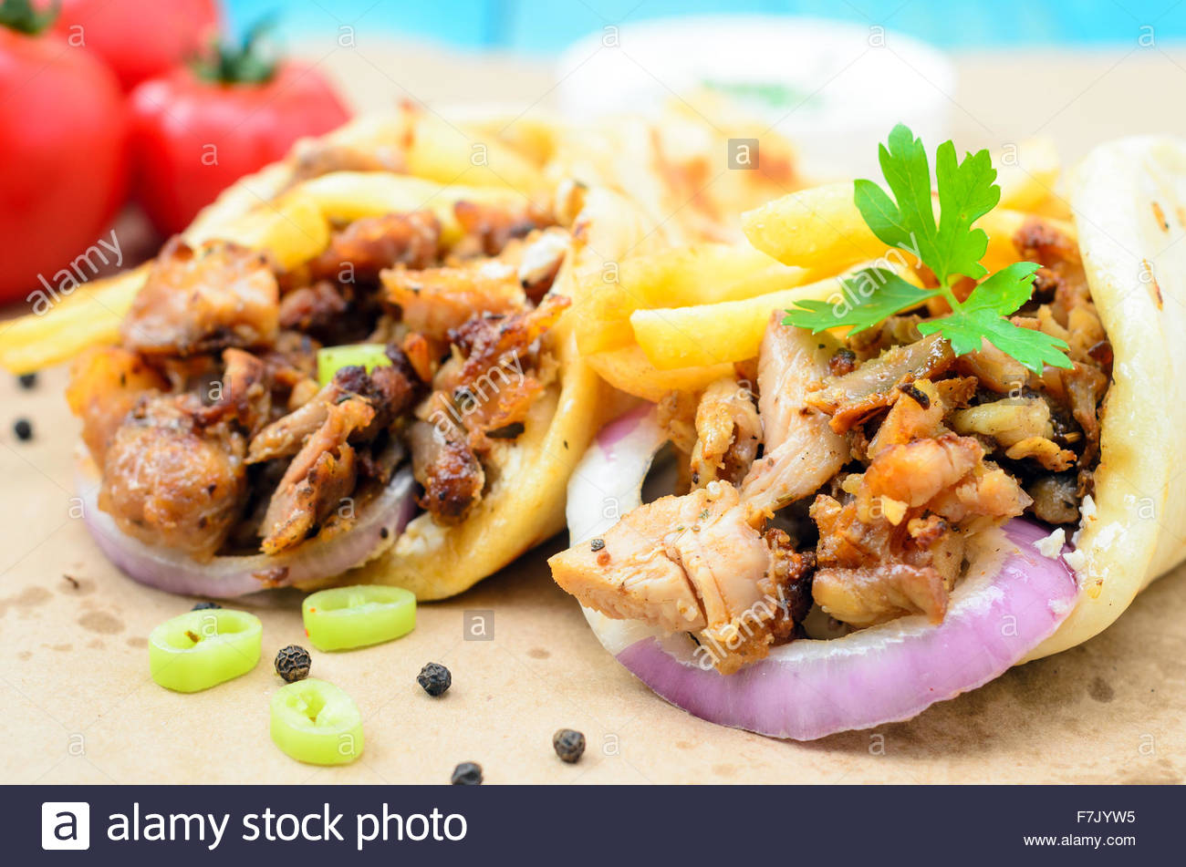 Stock Photo Traditiona Greek Pita Gyros With Meat Fried Potatoes Tomato Onion And Drink On Brown Paper Placed On Blue Wooden Table