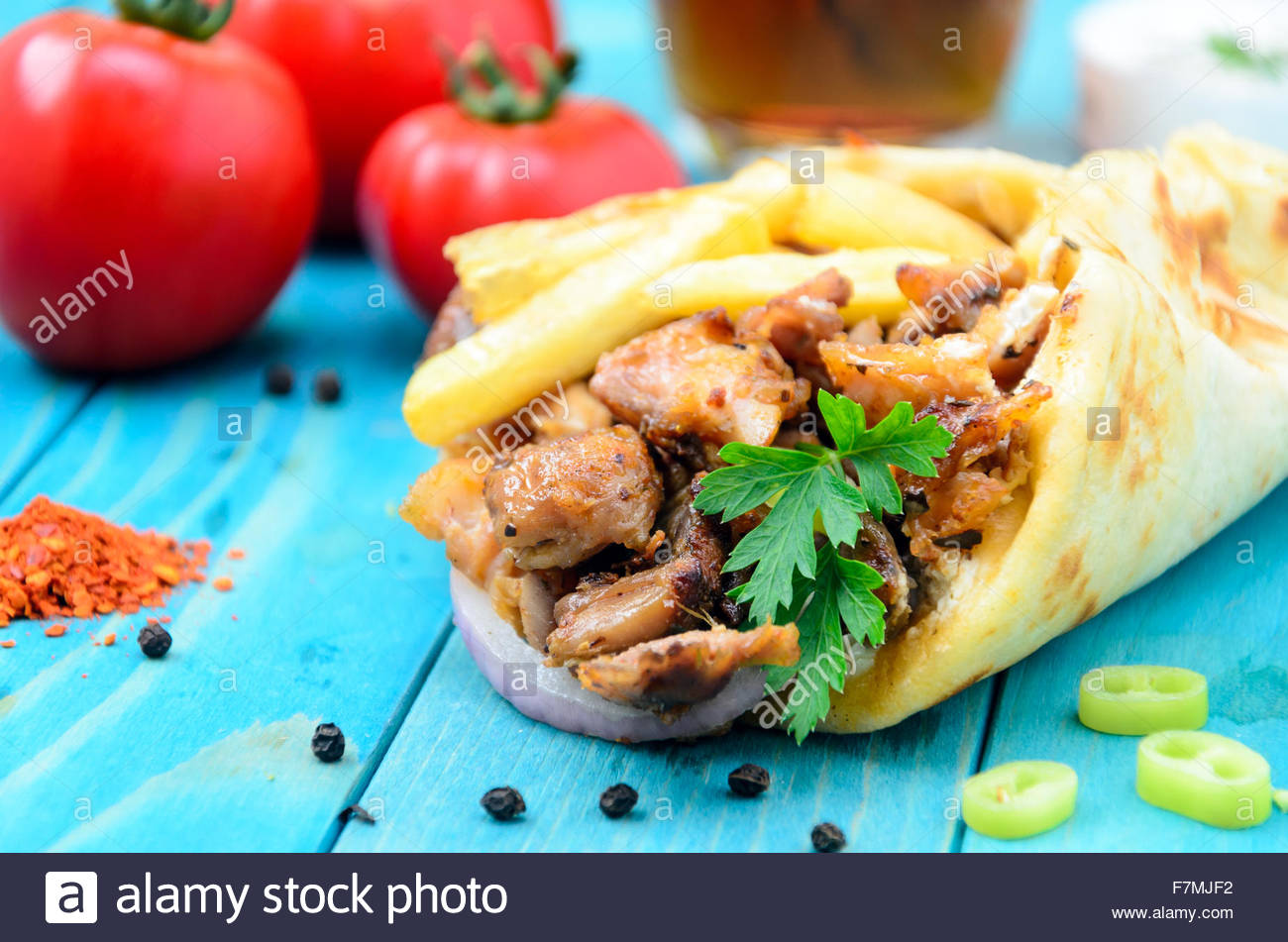 Plate Of Traditional Greek Gyros With Meat Fried Potatoes Tomato And Onion On Light Blue Wooden Table