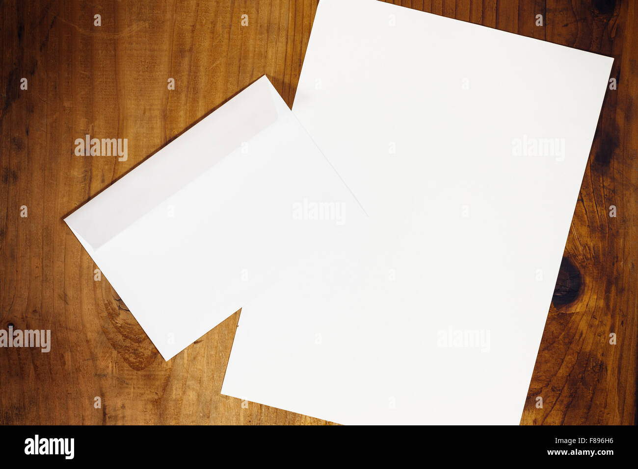 blank white envelope and letter paper on wooden office desk retro toned top view