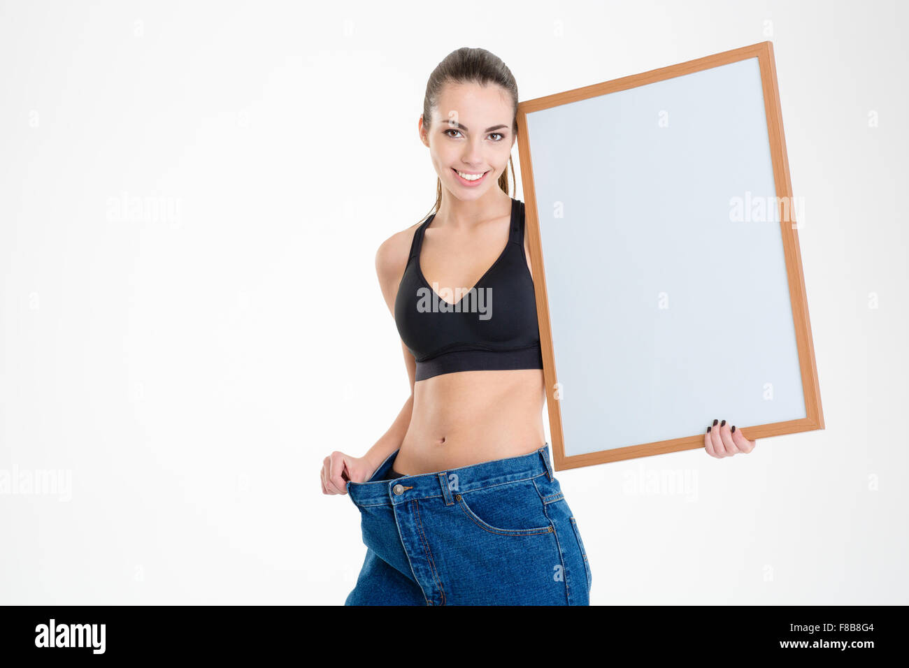 Background image too big - Smiling Cute Fitness Girl In Old Jeans Became Too Big Holding Blank Board Isolated Over White Background