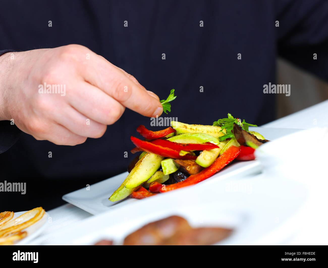 handsome chef dressed in black uniform decorating tasty food in