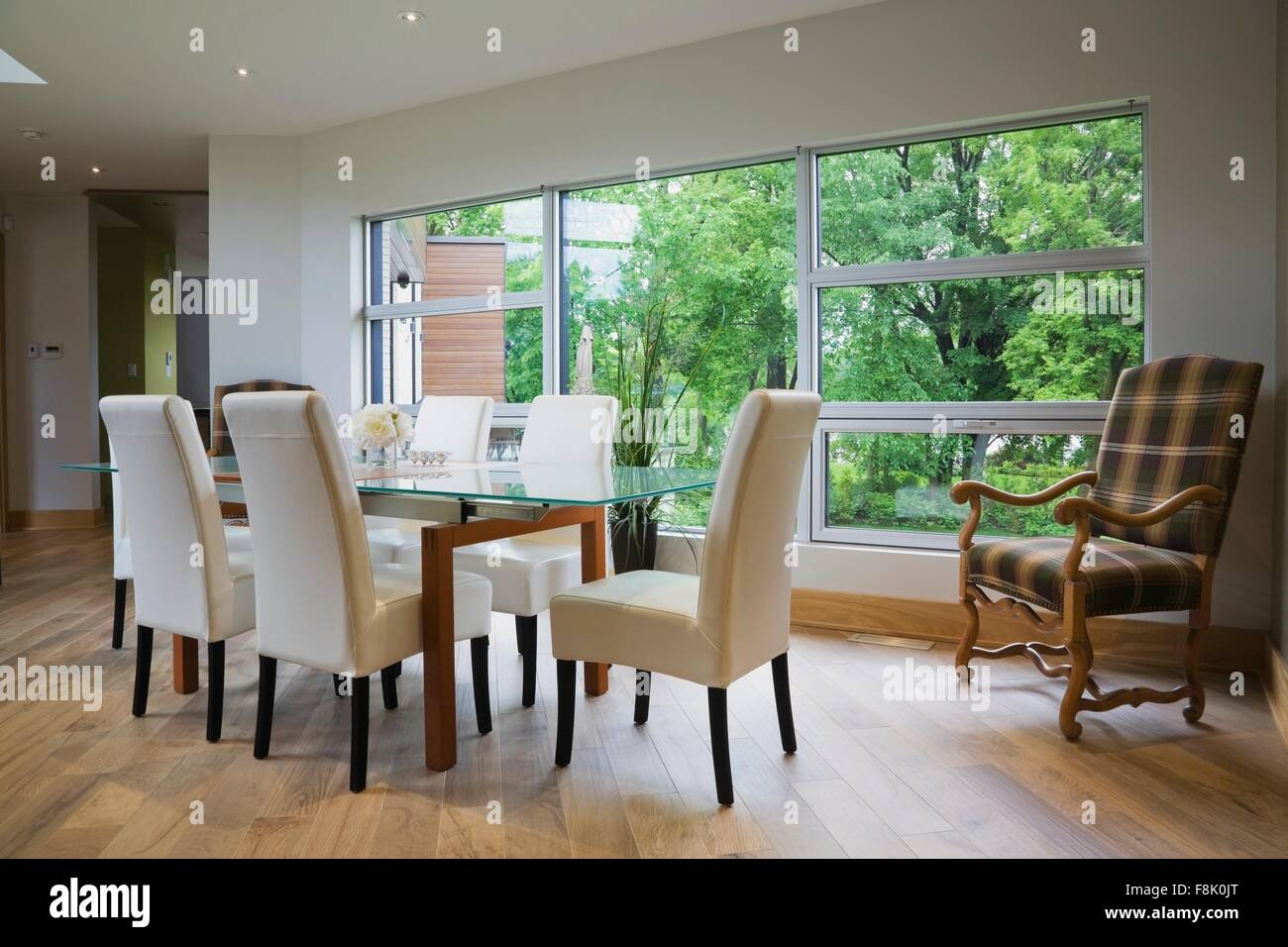 Glass Dining Table And Leather Chairs In Front Of Large Window In Modern Dining  Room