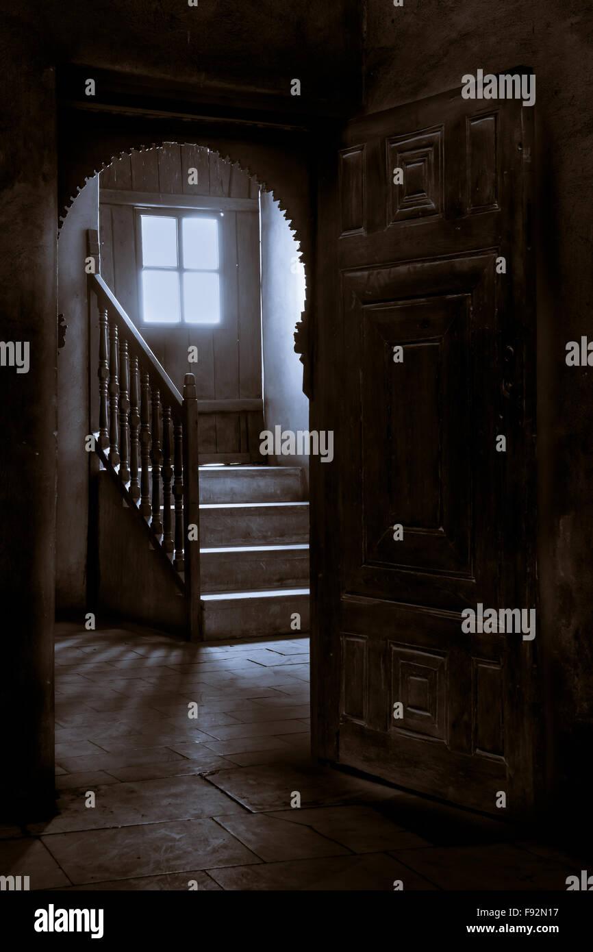 Dark room with light through door - Stock Photo Wooden Door Leading To A Dark Room With Window Revealing High Levels Of Light