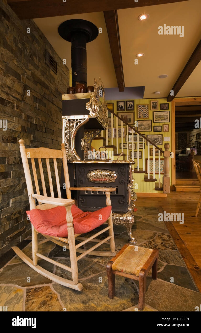 Old wooden chair styles - Old Wooden Rocking Chair Next To An Antique Royal Model Wood Cooking Stove In The Dining Room Inside A Country Cottage Style
