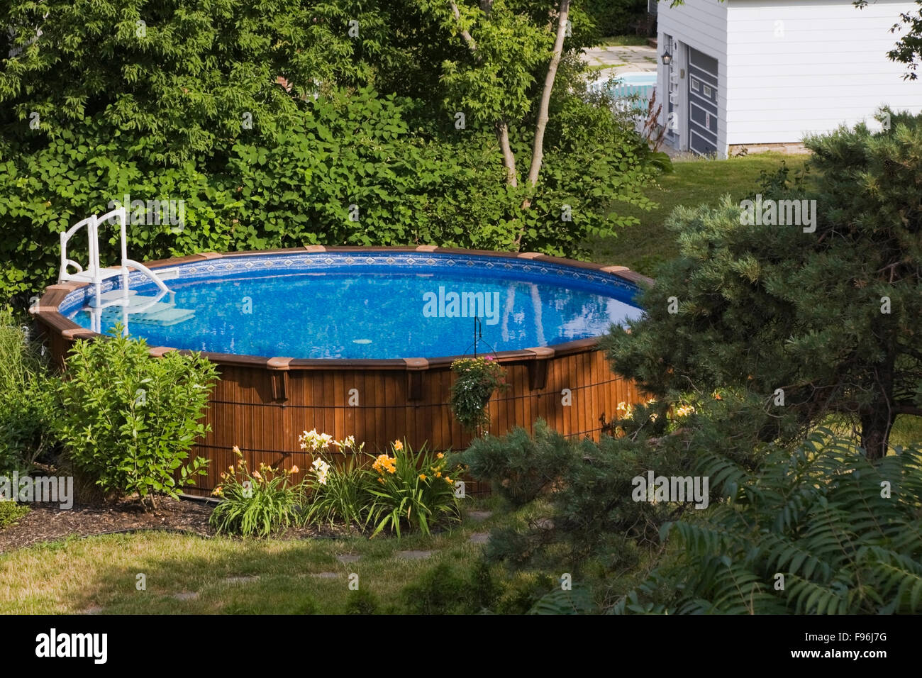 above ground cedar wood swimming pool in a residential backyard in