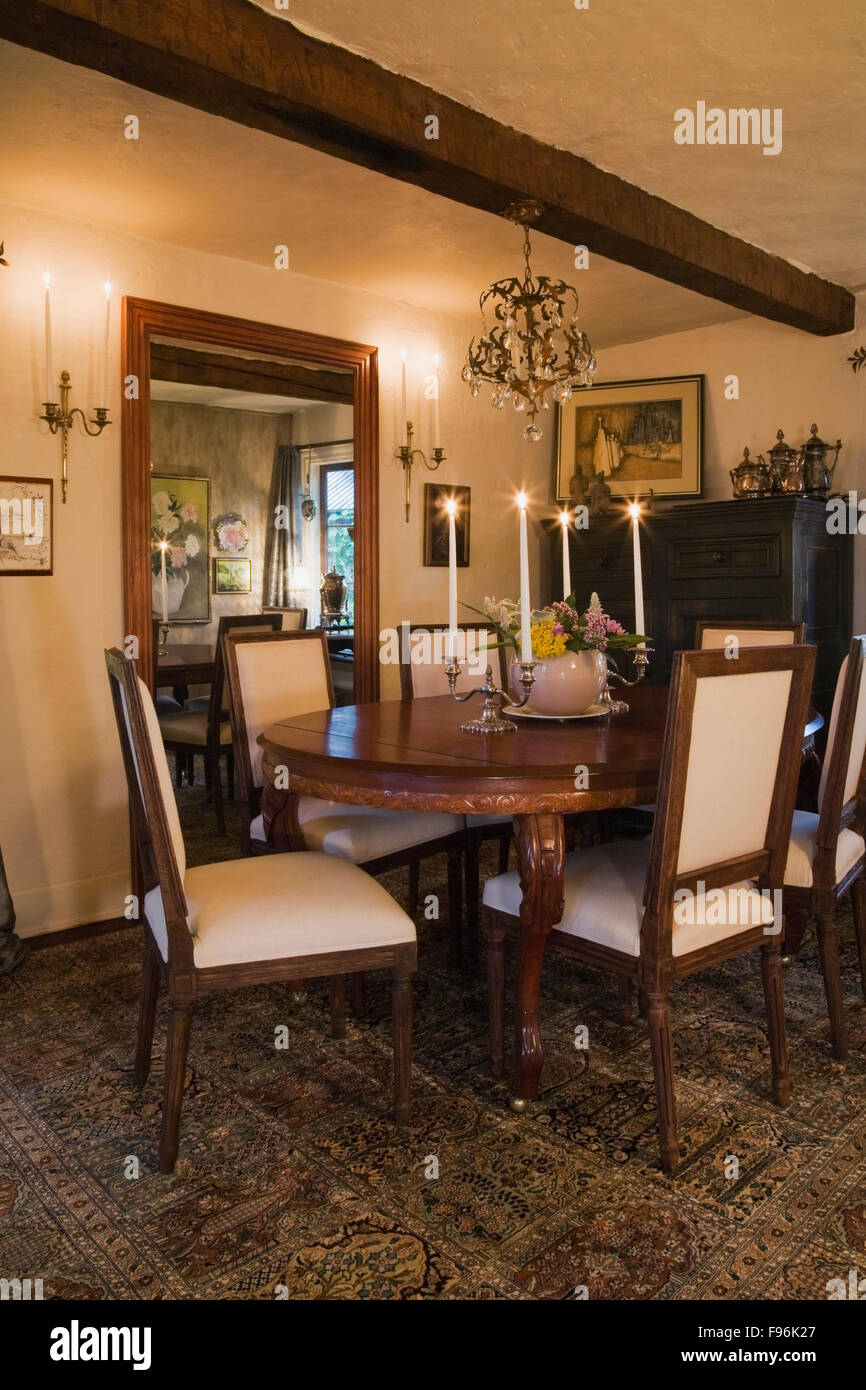 Antique Wooden Oval Table And Upholstered Chairs In The Dining Room Inside An Old 1809 Cottage Style Residential Home Quebec