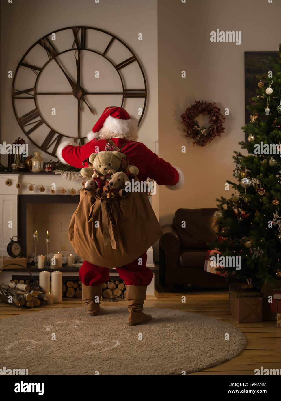santa claus putting gifts in socks on fireplace at home stock