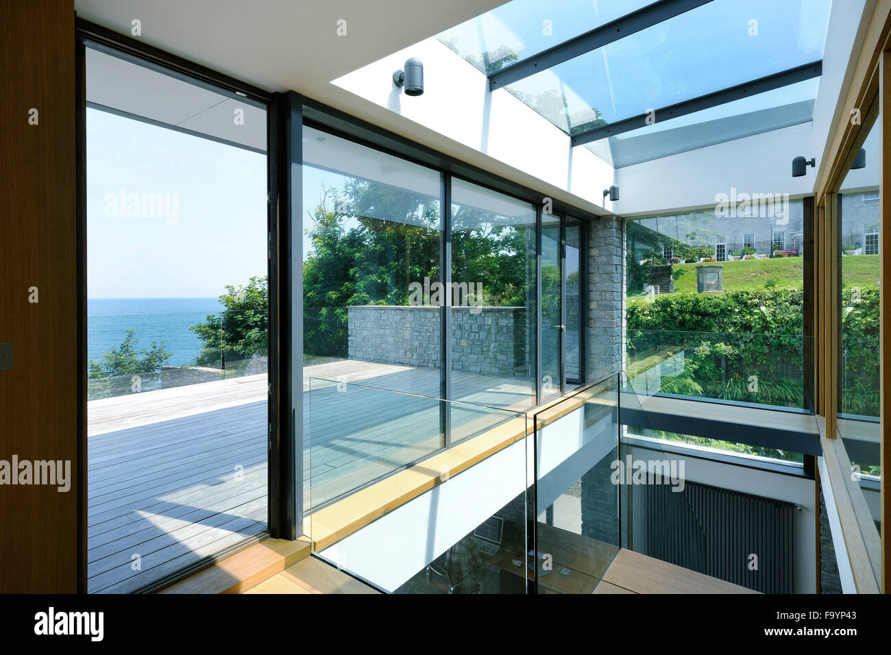 large sliding glass doors open floor to ceiling glass panels a low profile building in a seaside location: large sliding patio doors