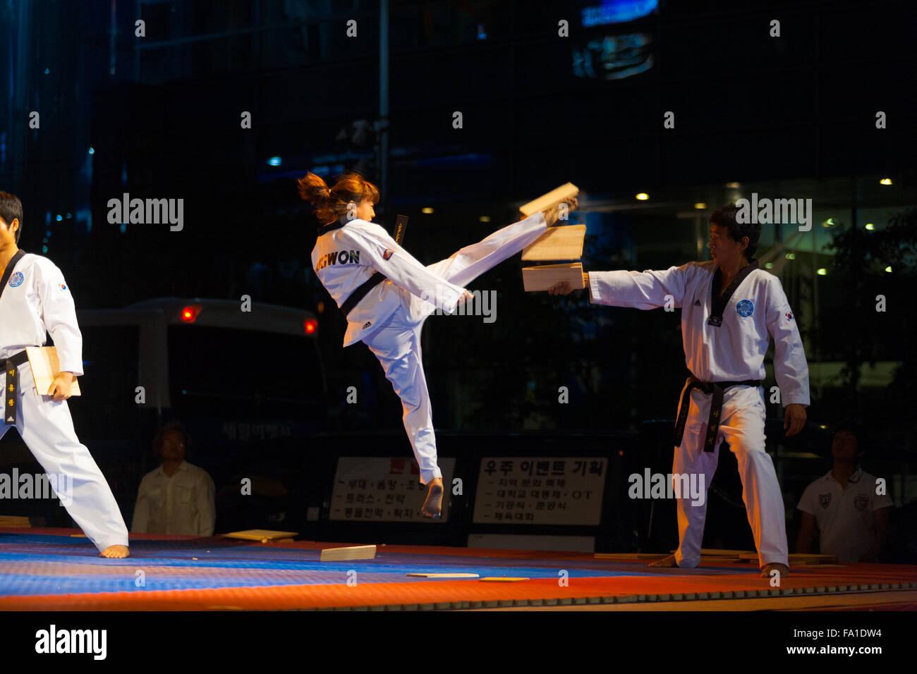 A Taekwondo Black Belt Female Teenager Jumping In Midair Kicking And  Breaking A Wood