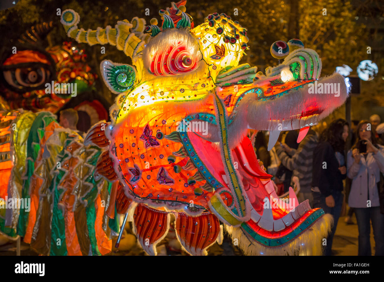illuminated dragon at san francisco chinese new year night parade with woman in background taking picture - San Francisco Chinese New Year