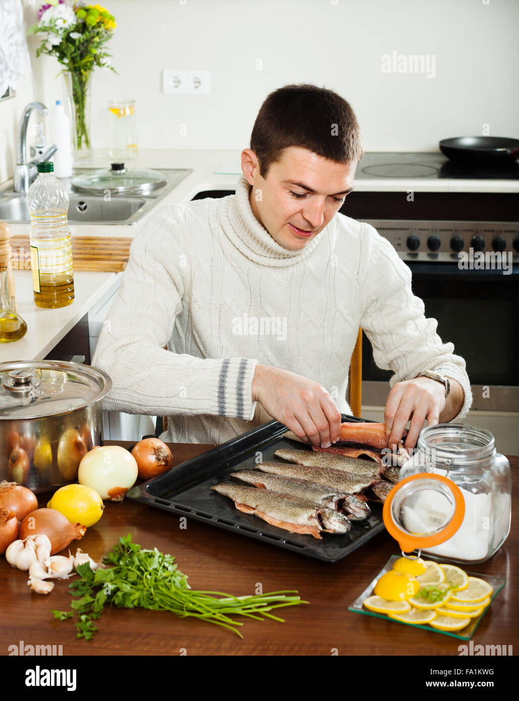 Home Kitchen Cooking Guy Cooking Raw Fish In Roasting Pan At Home Kitchen Stock Photo