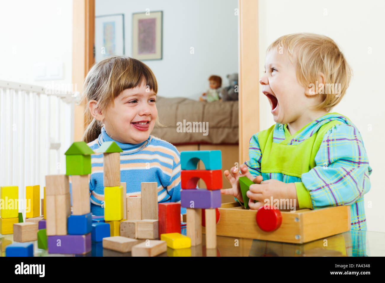 Toys For Siblings : Emotional happy siblings playing with wooden toys in home