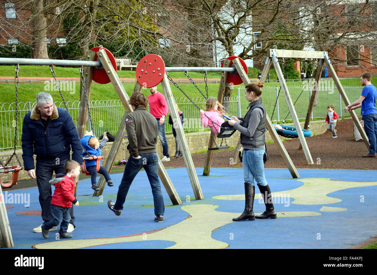 Parents and children playing on the swings in the park ...
