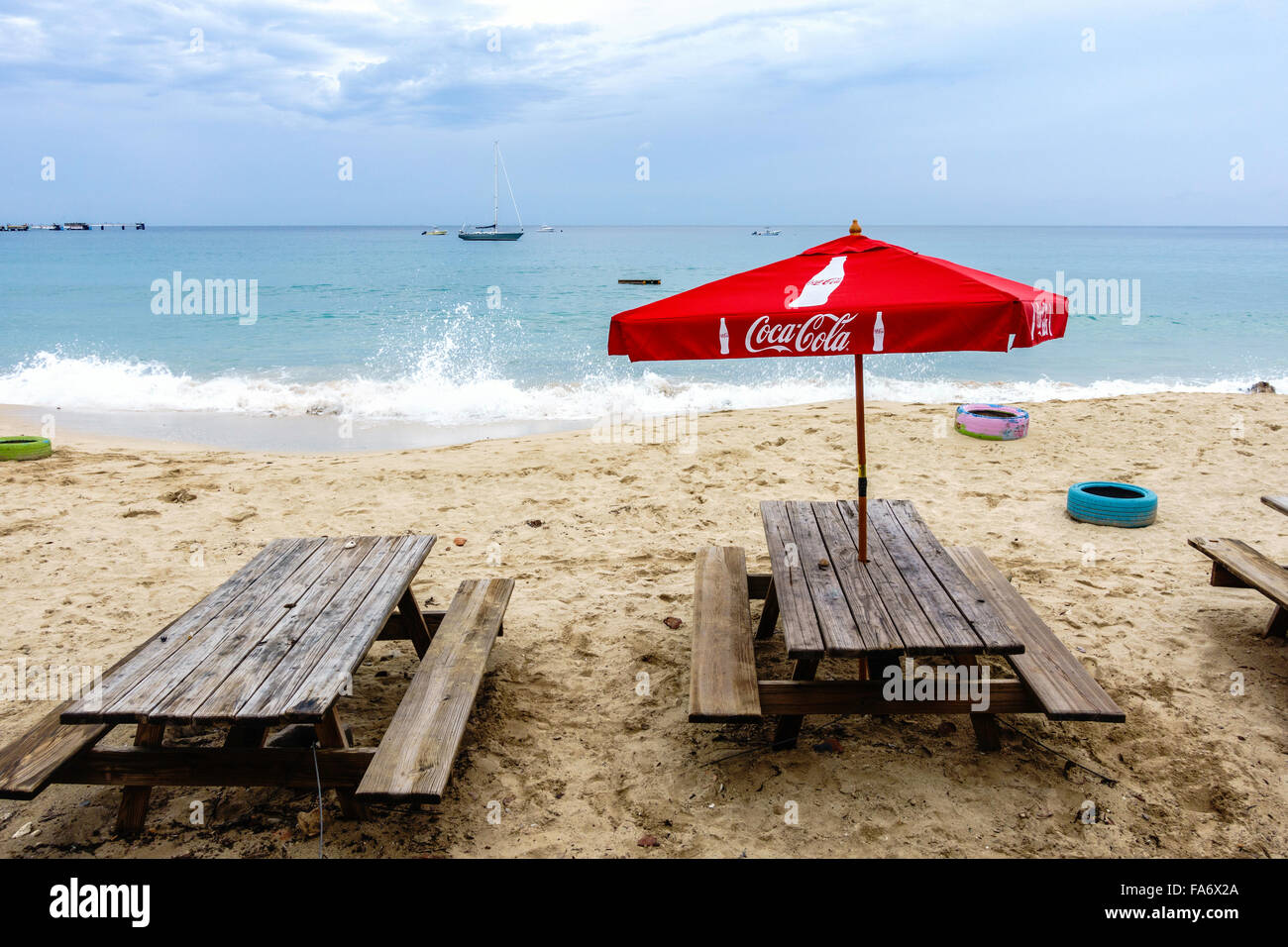 Weatherbeaten Wooden Picnic Tables With A Red CocaCola Umbrella On A  Caribbean Beach.   Stock