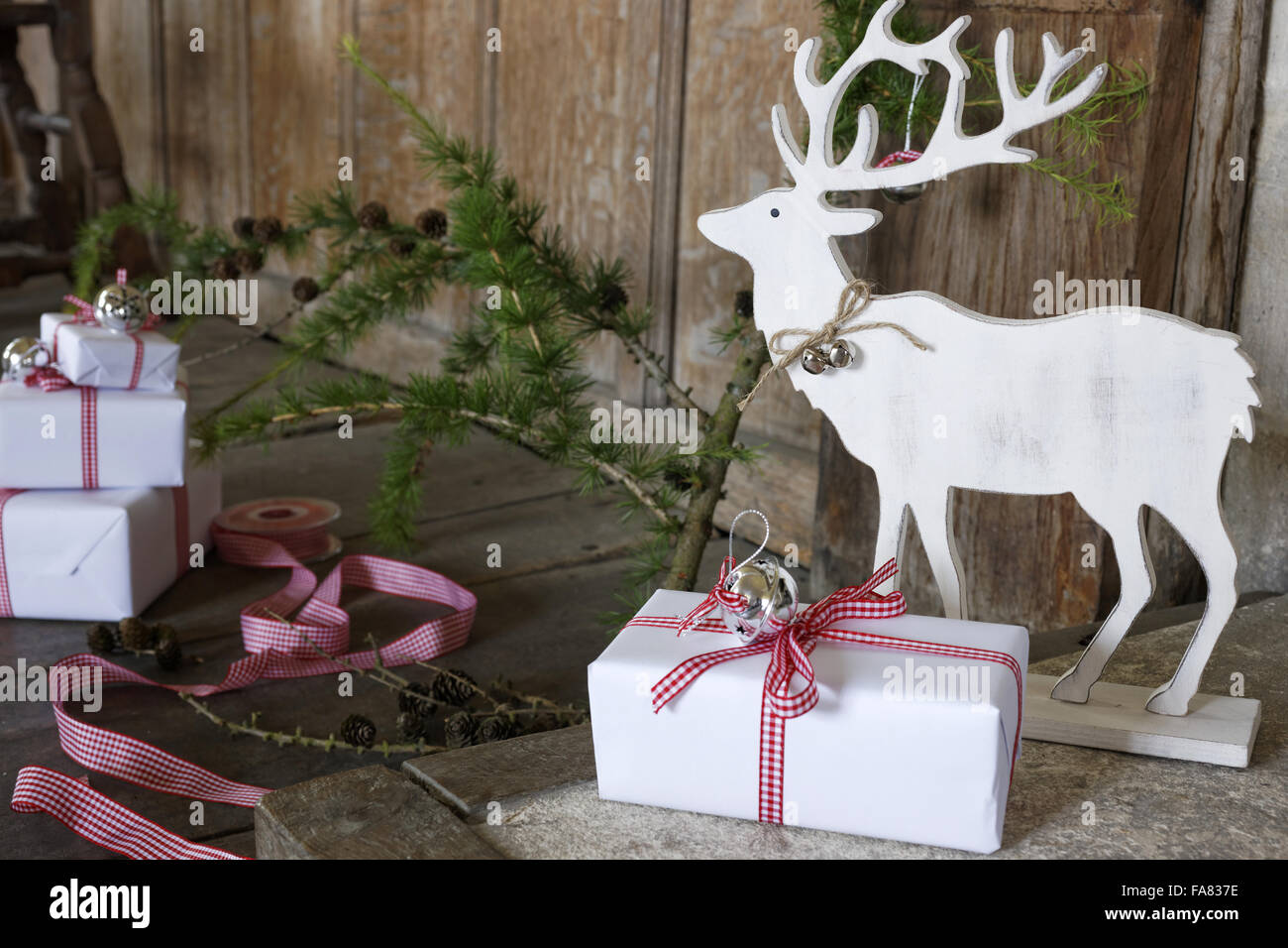 white wooden reindeer ornament with gift wrapped christmas