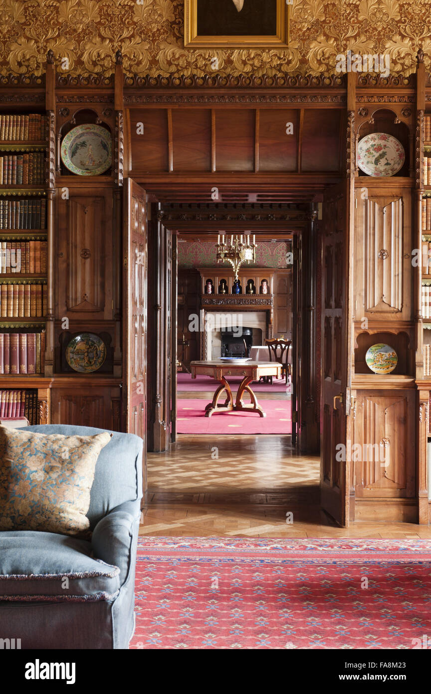 View from the Library through the door to the Morning Room at Knightshayes Court Devon. The bookcases are in a Gothic style with linenfold panelling by ... & View from the Library through the door to the Morning Room at Stock ...