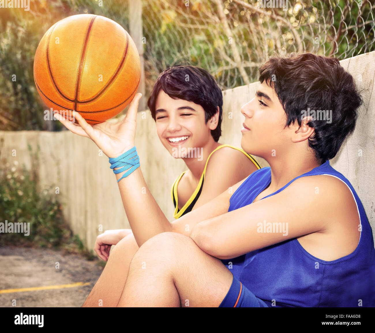 cute basketball players sitting and resting in timeout  two active stock photo  royalty free
