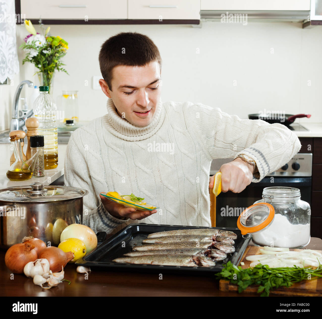 Home Kitchen Cooking Guy Cooking Fish With Lemon In Baking Sheet At Home Kitchen Stock