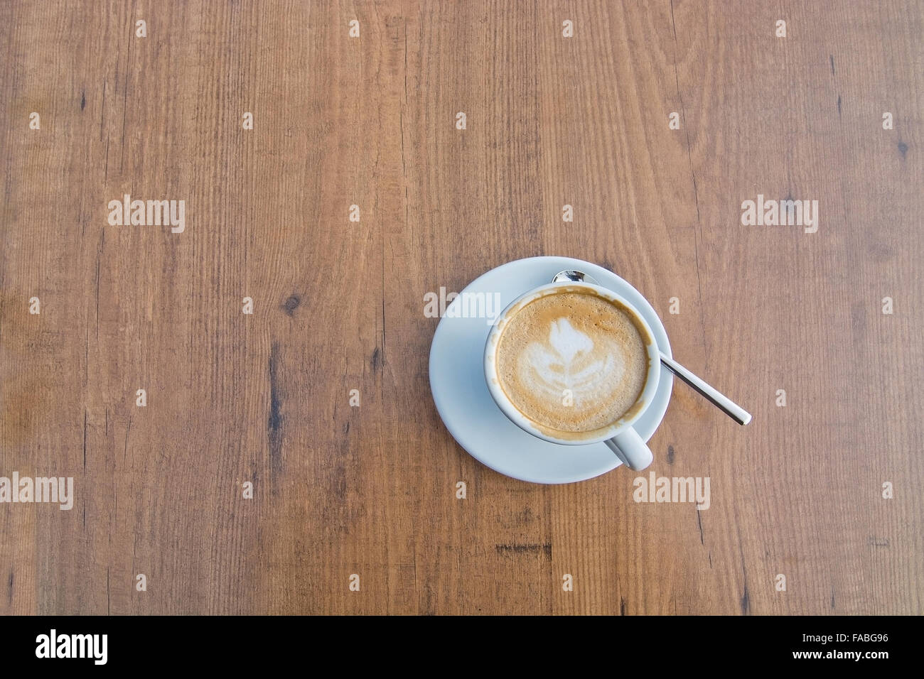 White Cup With Foaming Cappuccino Coffee And Spoon On Wood Table - Cappuccino coffee table