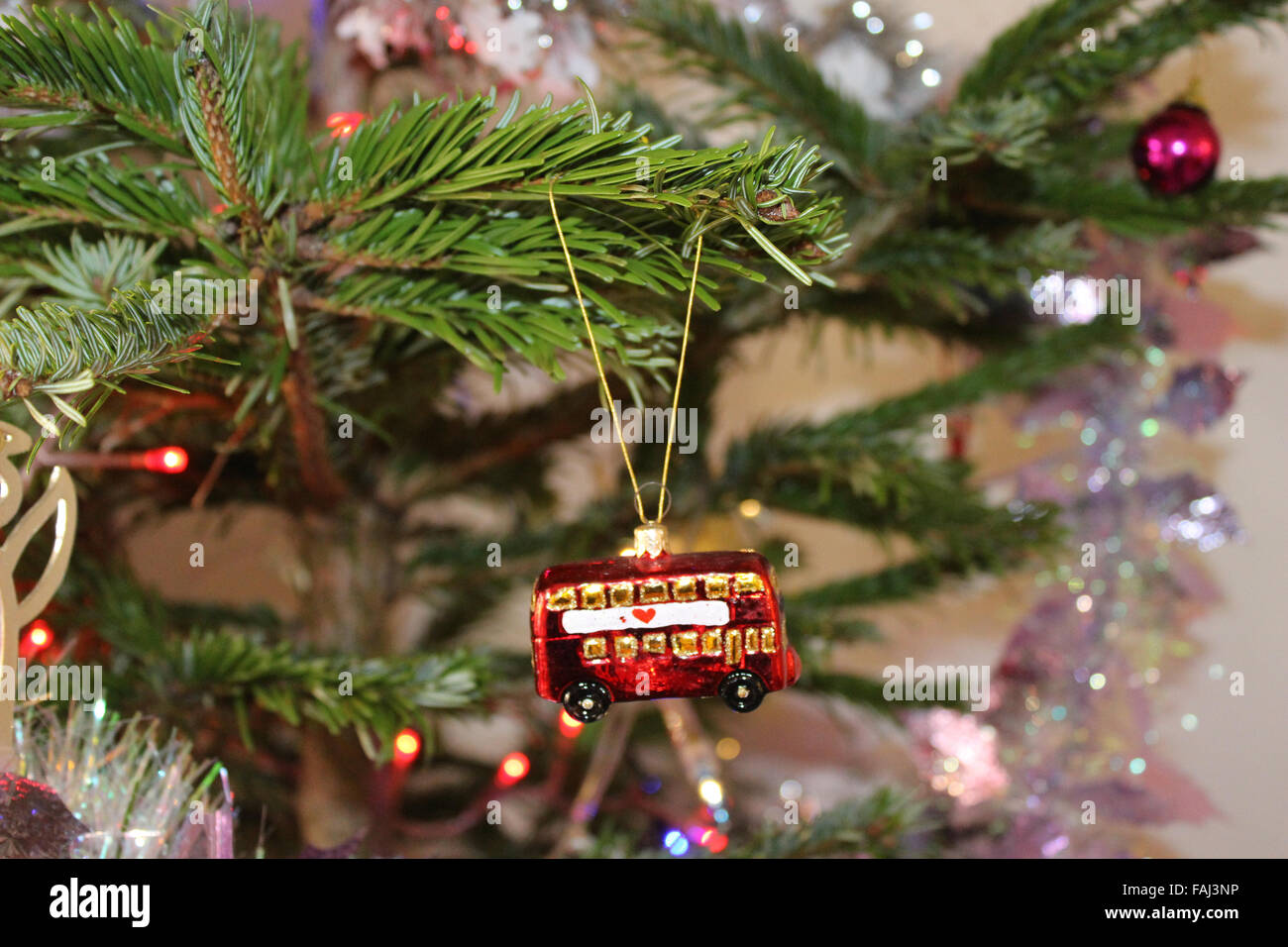 A London bus Christmas decoration hangs from a Christmas tree