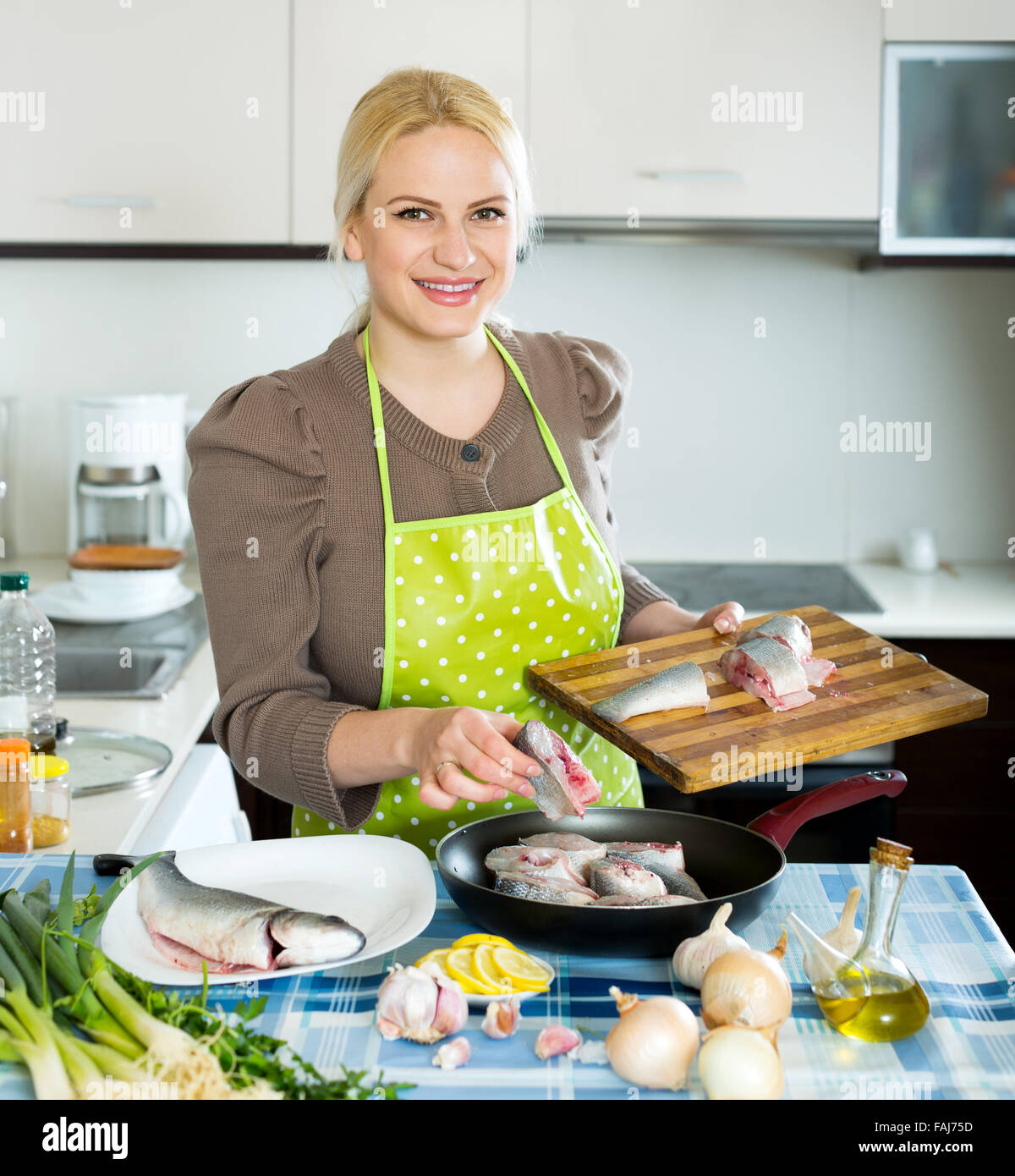 Home Kitchen Cooking Happy Blonde Woman Cooking Fish In Frying Pan At Home Kitchen