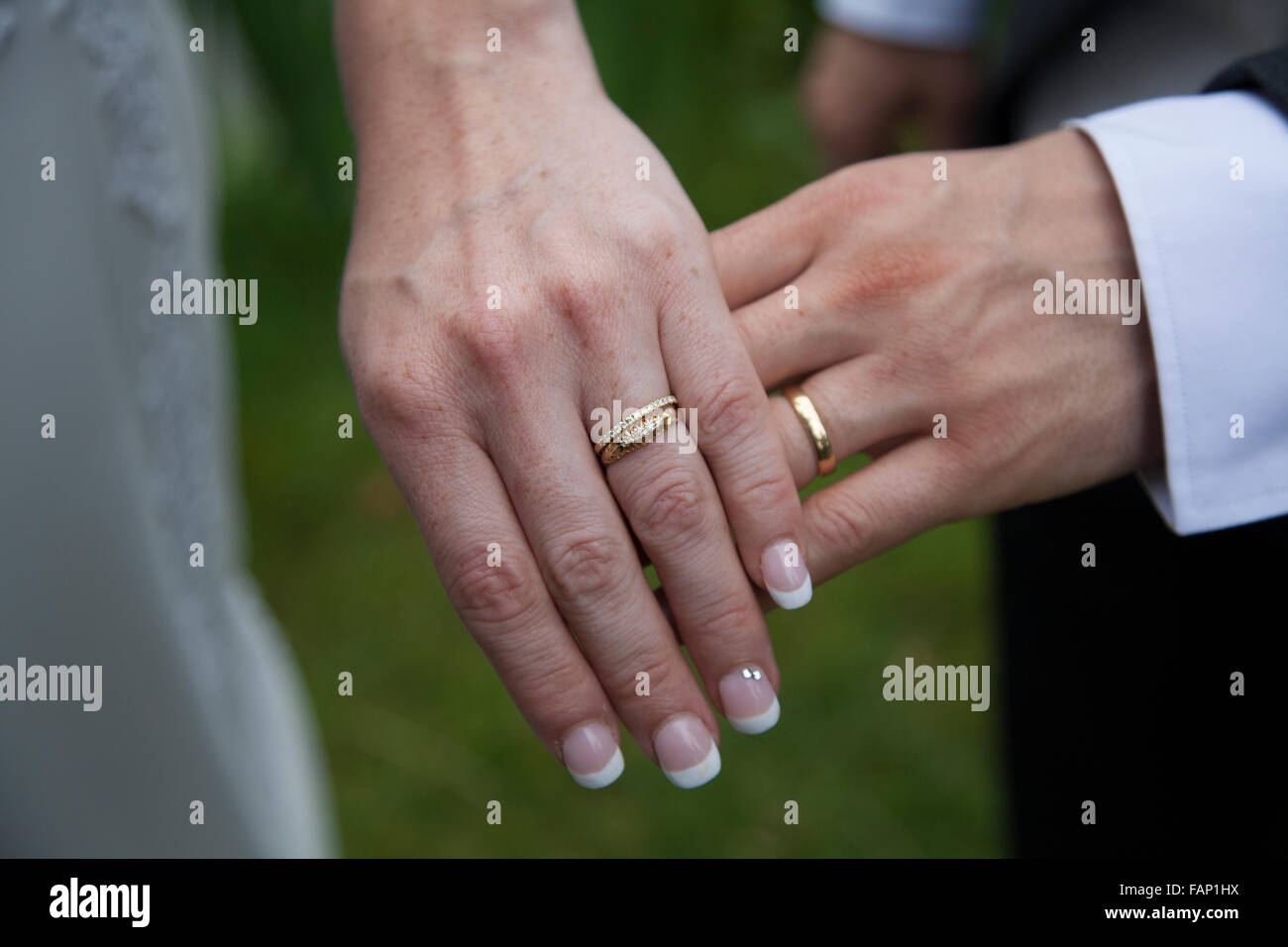 bride and grooms wedding rings hand held together both wedding bands showing on their wedding day - Wedding Rings On Hands