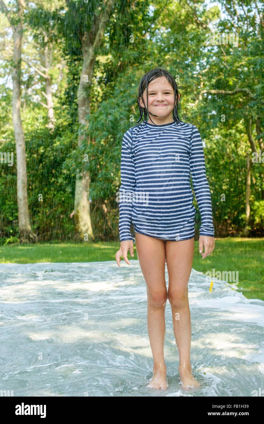 youngster girls Portrait of young girl standing on slip n slide water mat in garden