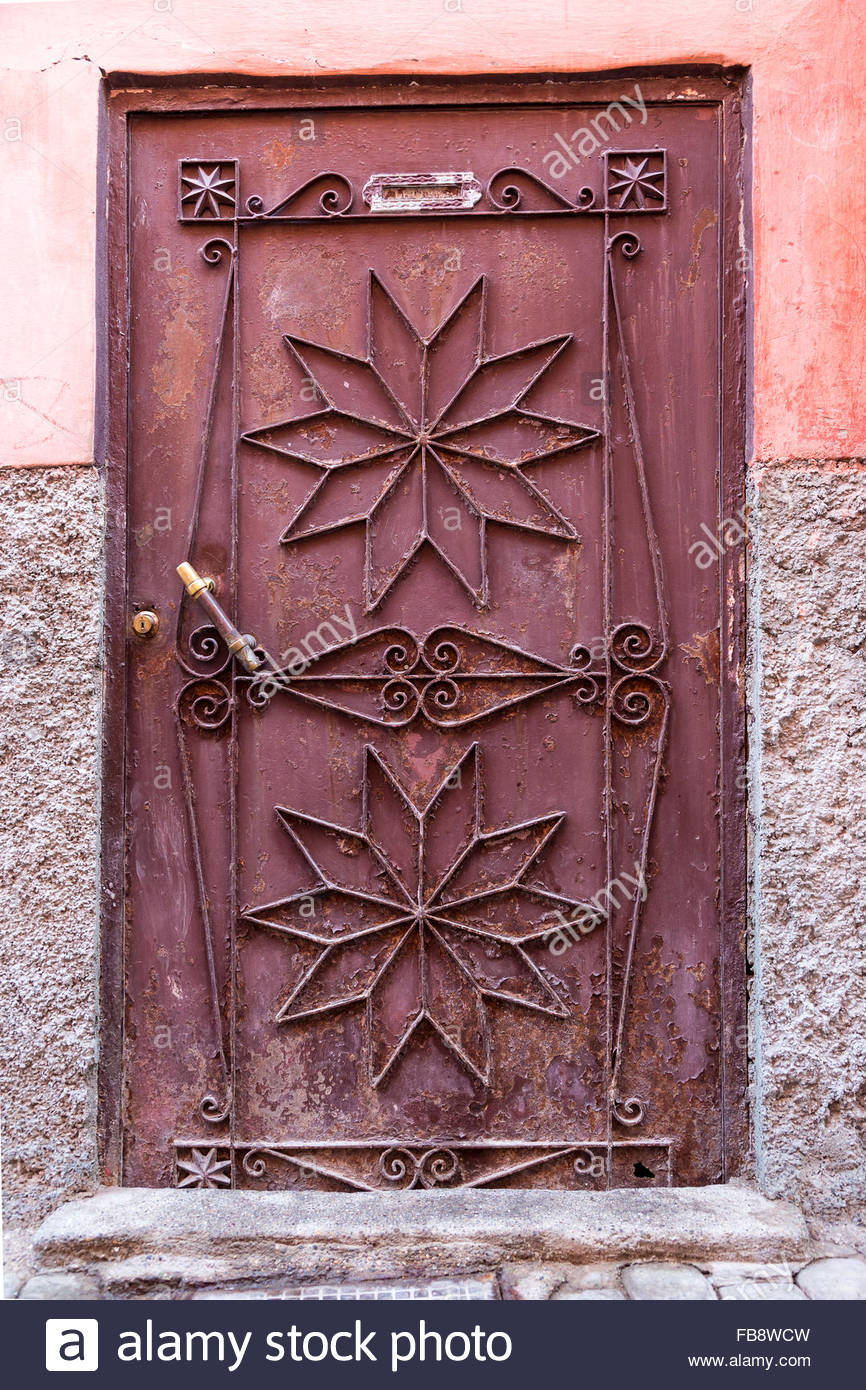 Metalwork door with star or flower shapes and flaking rusty red paintwork against a rough & Metalwork door with star or flower shapes and flaking rusty red ... pezcame.com