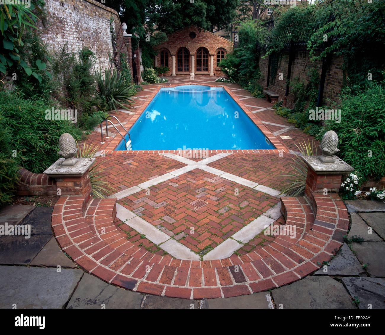 brick paving around turquoise rectangular swimming pool in large