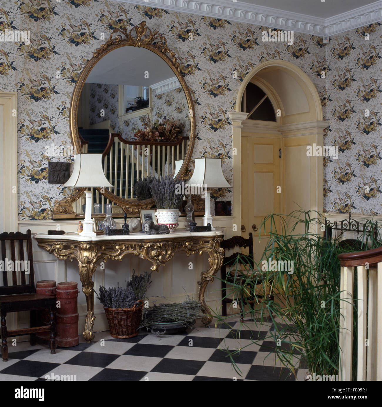 Large Oval Antique Mirror Above Gilt Antique Console Table With White Lamps  In Georgian Hall With Floral Wallpaper
