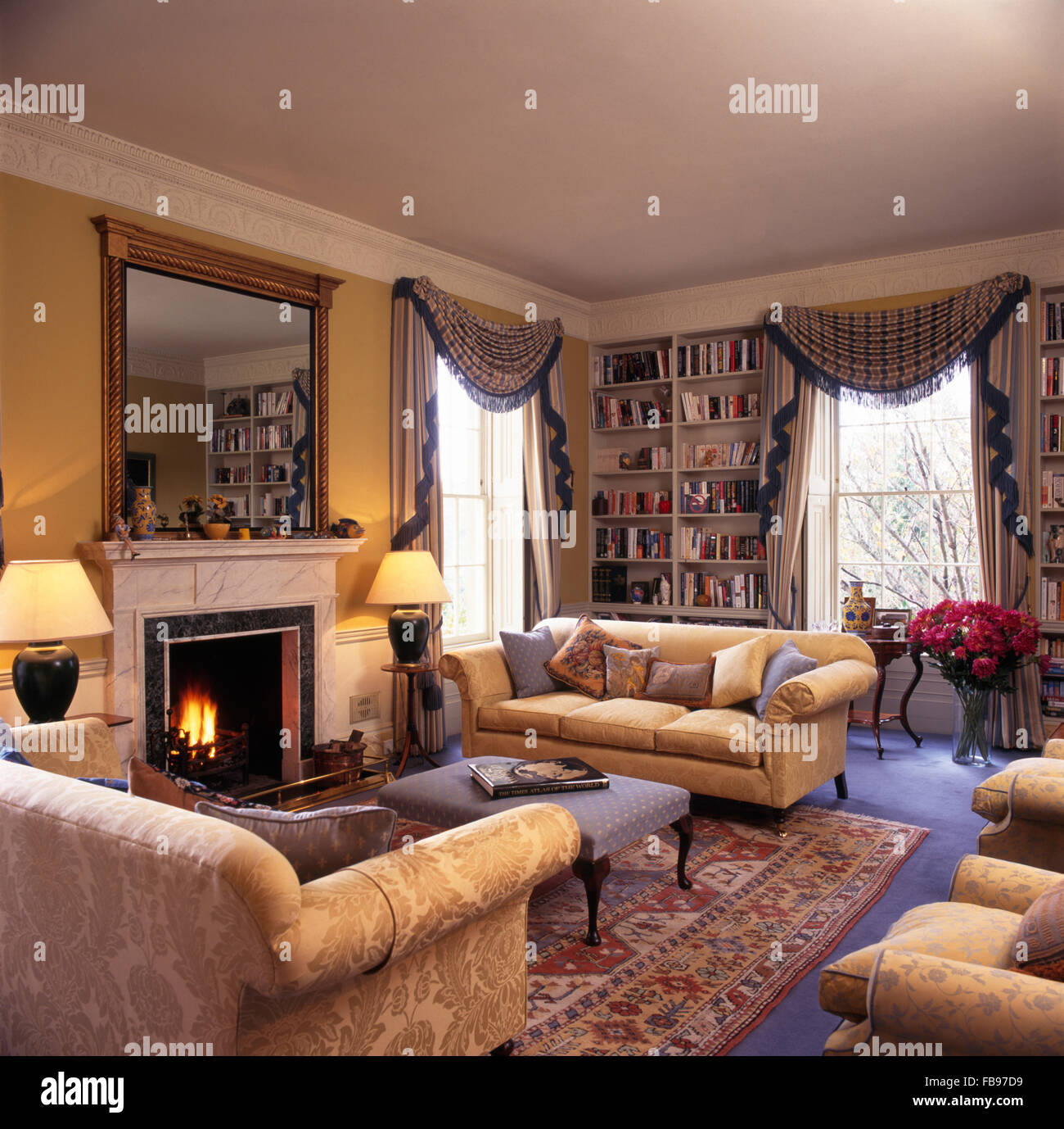 chesterfield sofas either side of fireplace with lighted fire in