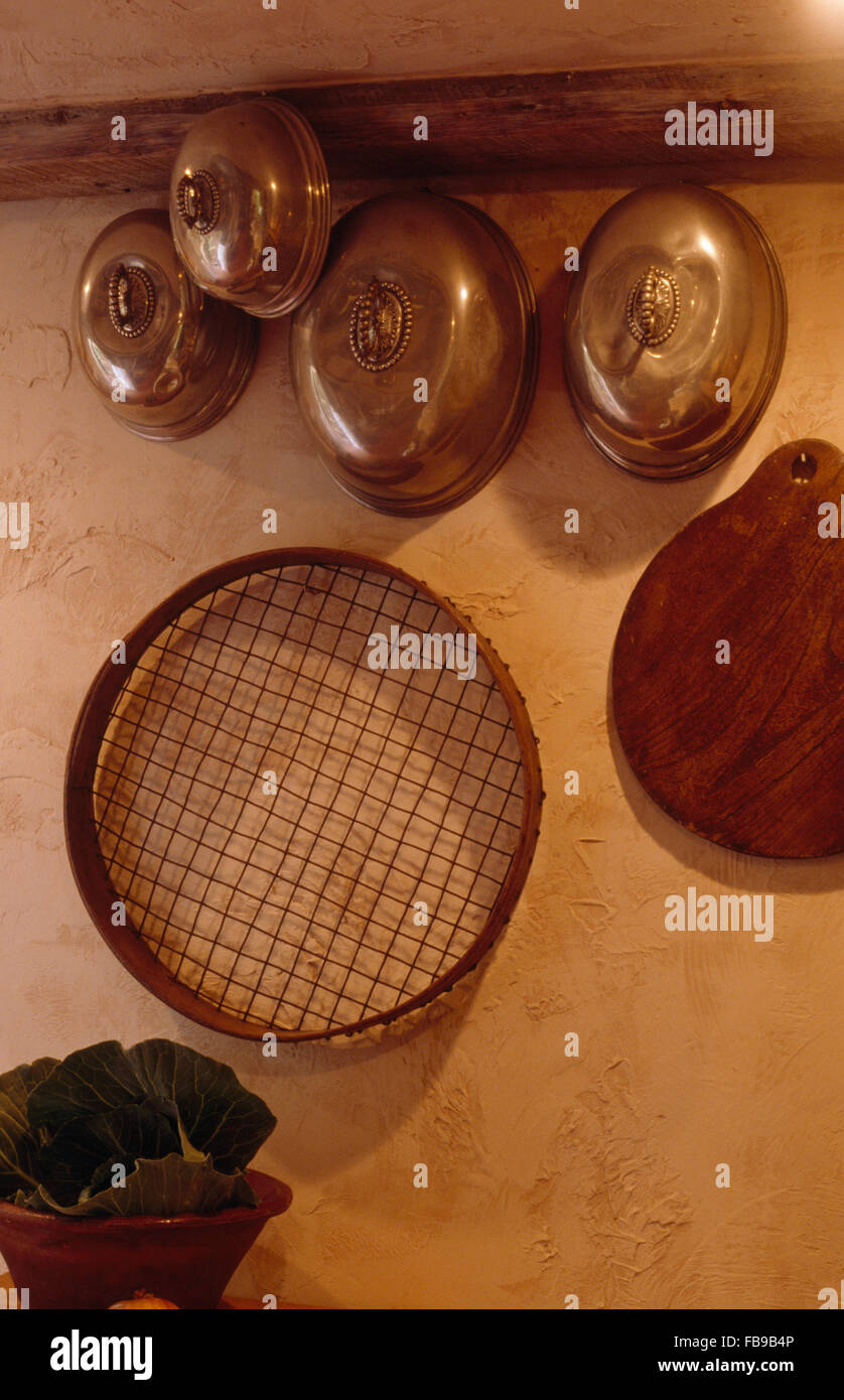 closeup of old copper pans and a sieve hanging on kitchen wall