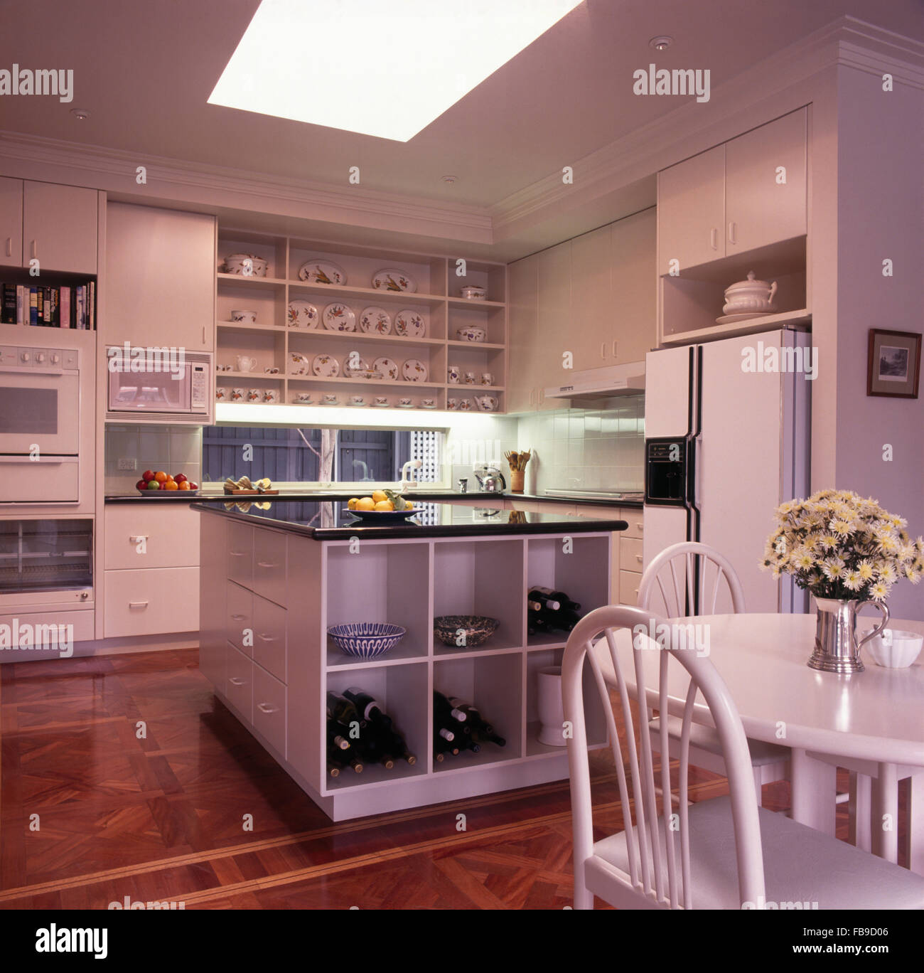 American style kitchen - Stock Photo White Dining Table And Chairs And An American Style Fridge Freezer In A White Kitchen With Open Cube Shelves In Island Unit