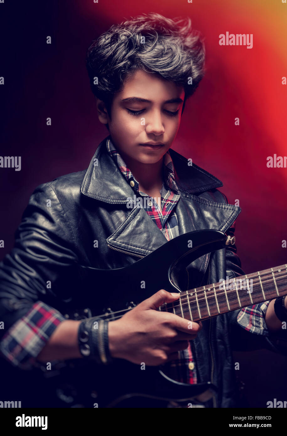 Closeup portrait of serious teen guy playing on guitar in the ...