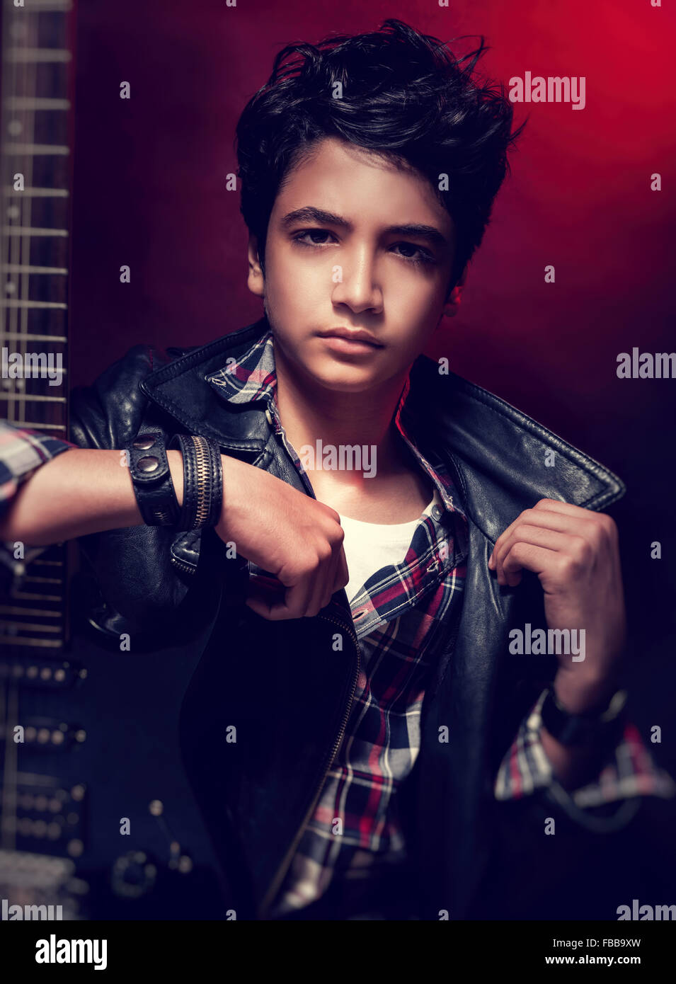 Attractive teen guy posing with guitar over dark red background ...