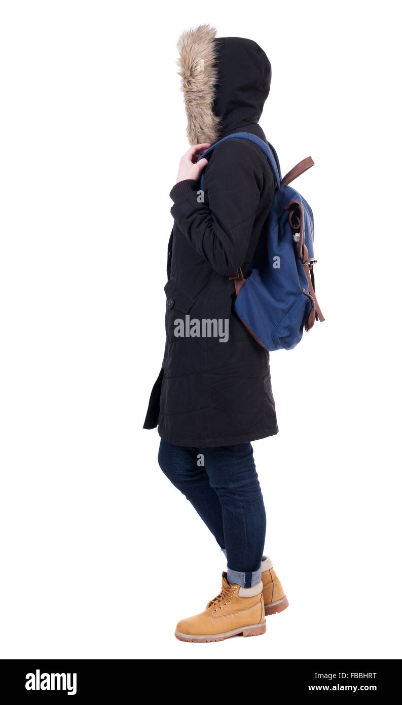 Back view woman in winter jacket with a backpack looking ...