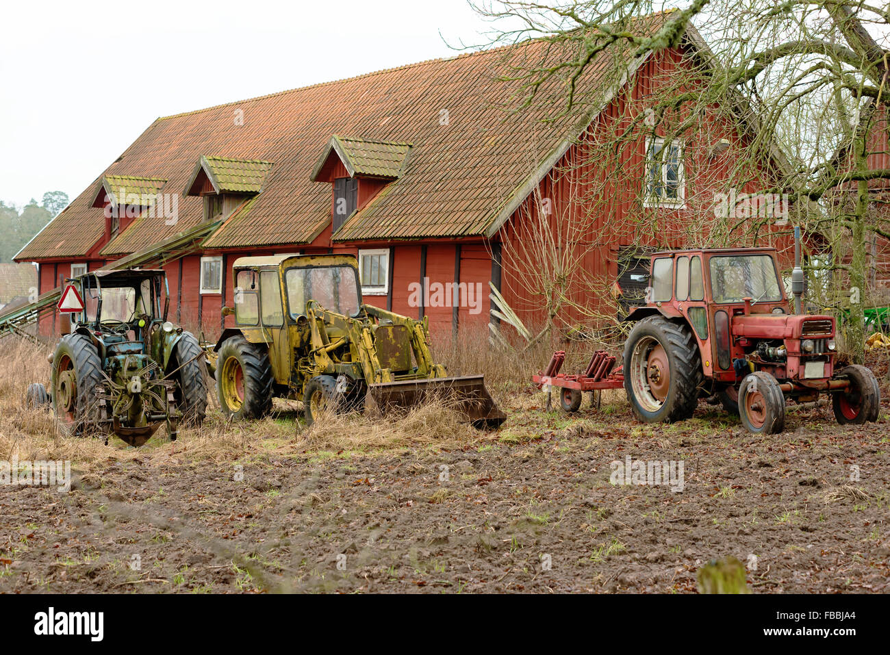 Old vintage tractors stand outside a farm building or barn for Building a tractor barn
