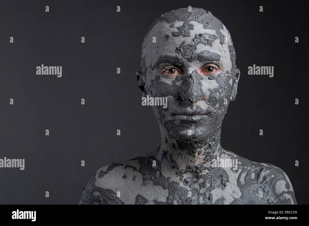 Statuesque woman in clay. Woman covered in clay. Spa treatment or ...