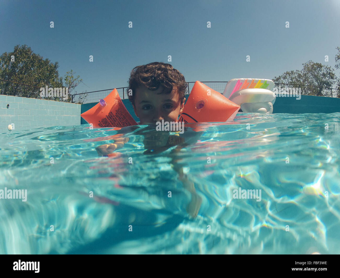 Swimming Pool Wings : Portrait of boy swimming in pool with water wings stock