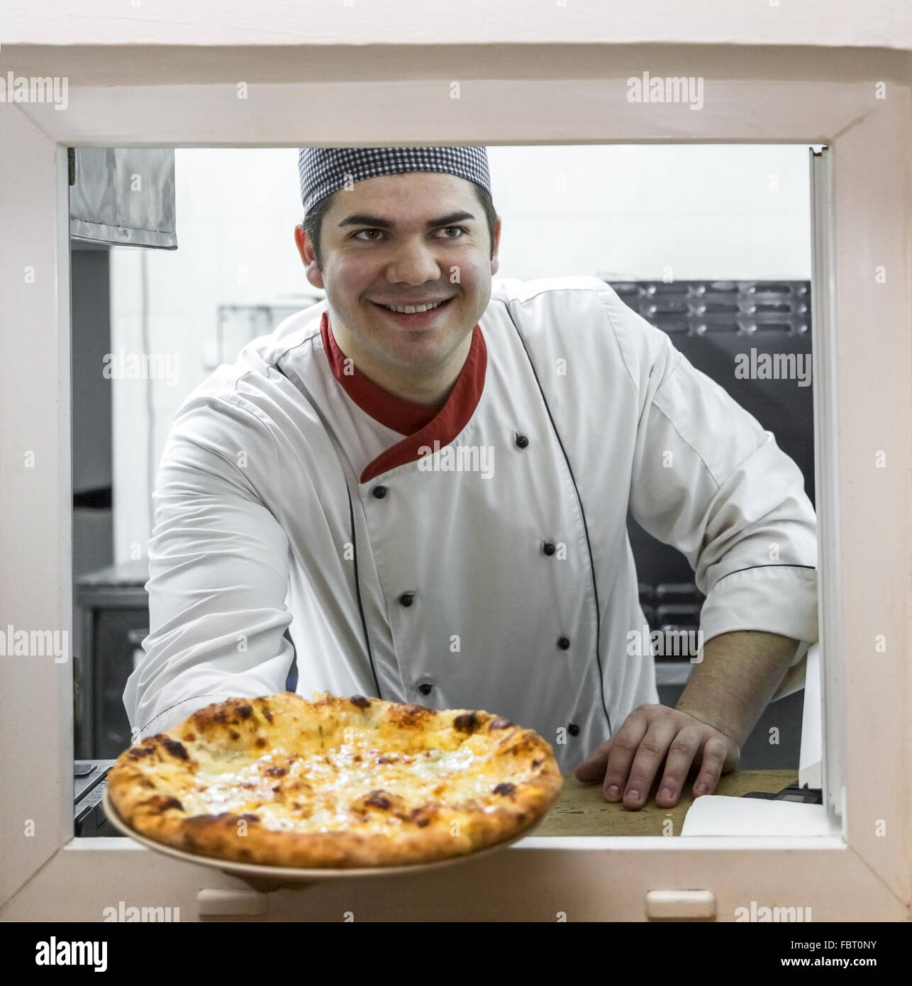 Happy chef offering a fresh pizza through the window of for Fresh chef kitchen