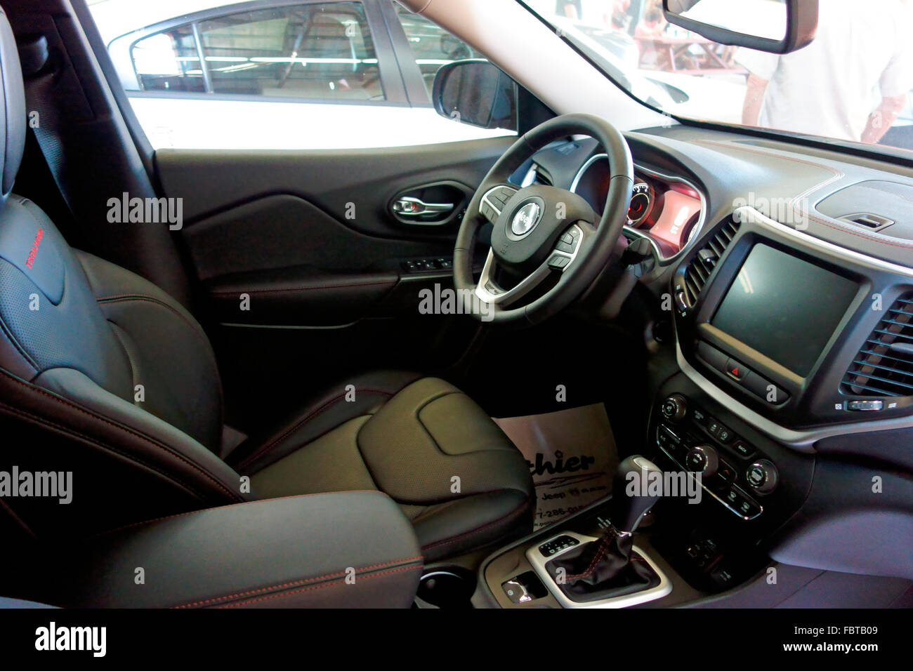 The front interior seats dash and steering wheel and navigation screen of a 2015 2016 jeep