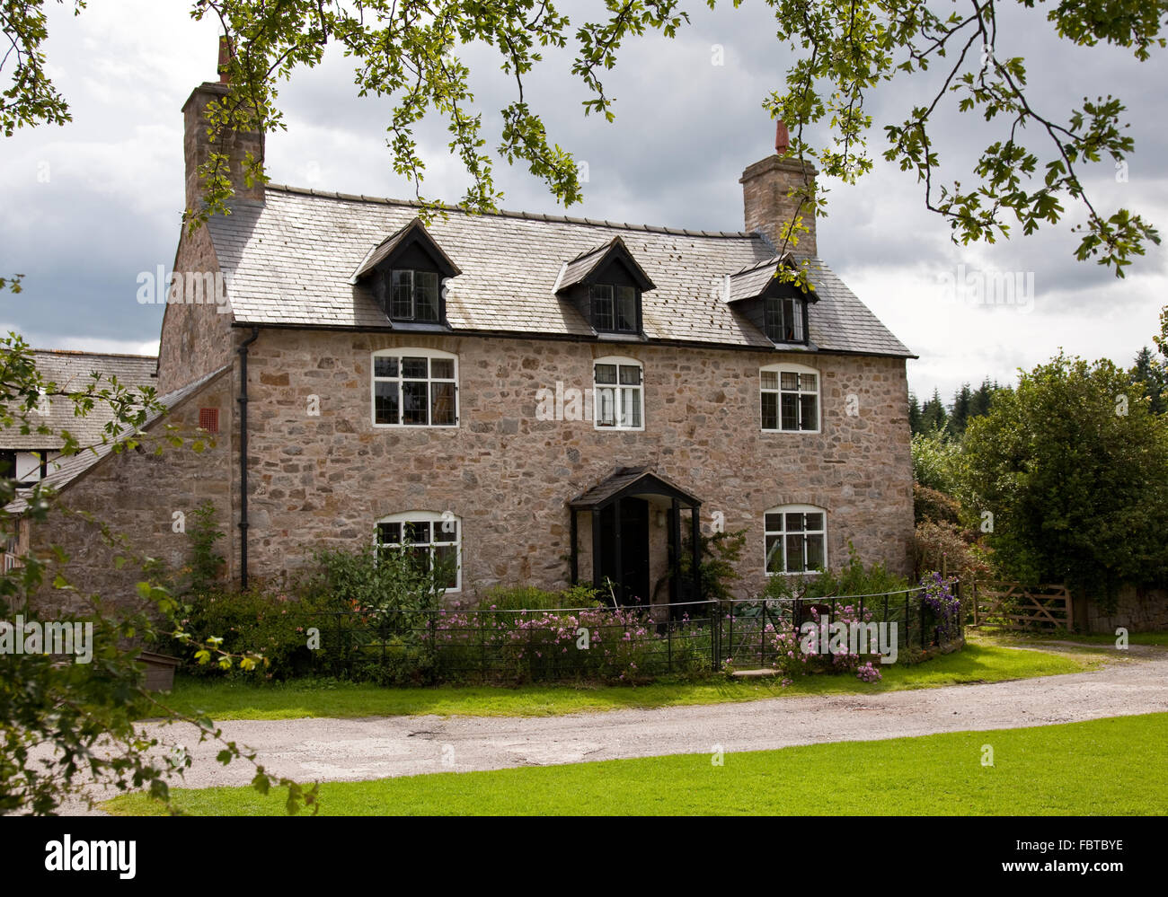 Rough Stone House With Dormer Windows And Surrounding Flowers Roses