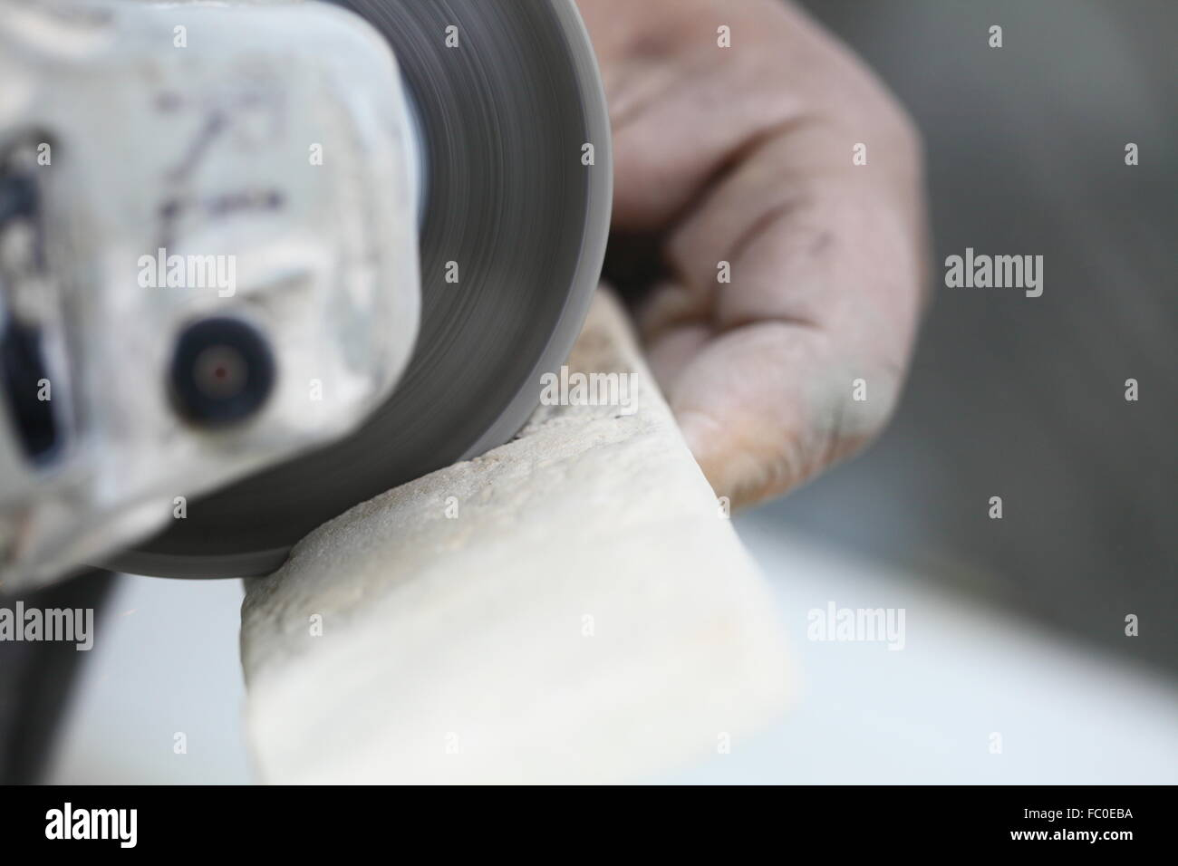 Worker cutting a tile using an angle grinder at construction site construction worker using an angle grinder cutting tile stock photo dailygadgetfo Image collections