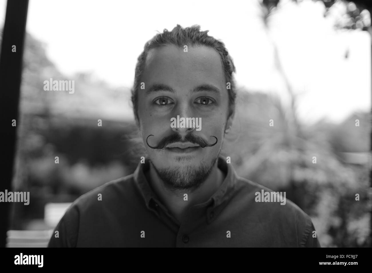 Head shot with mustache man bun and nose ring in black and white ...