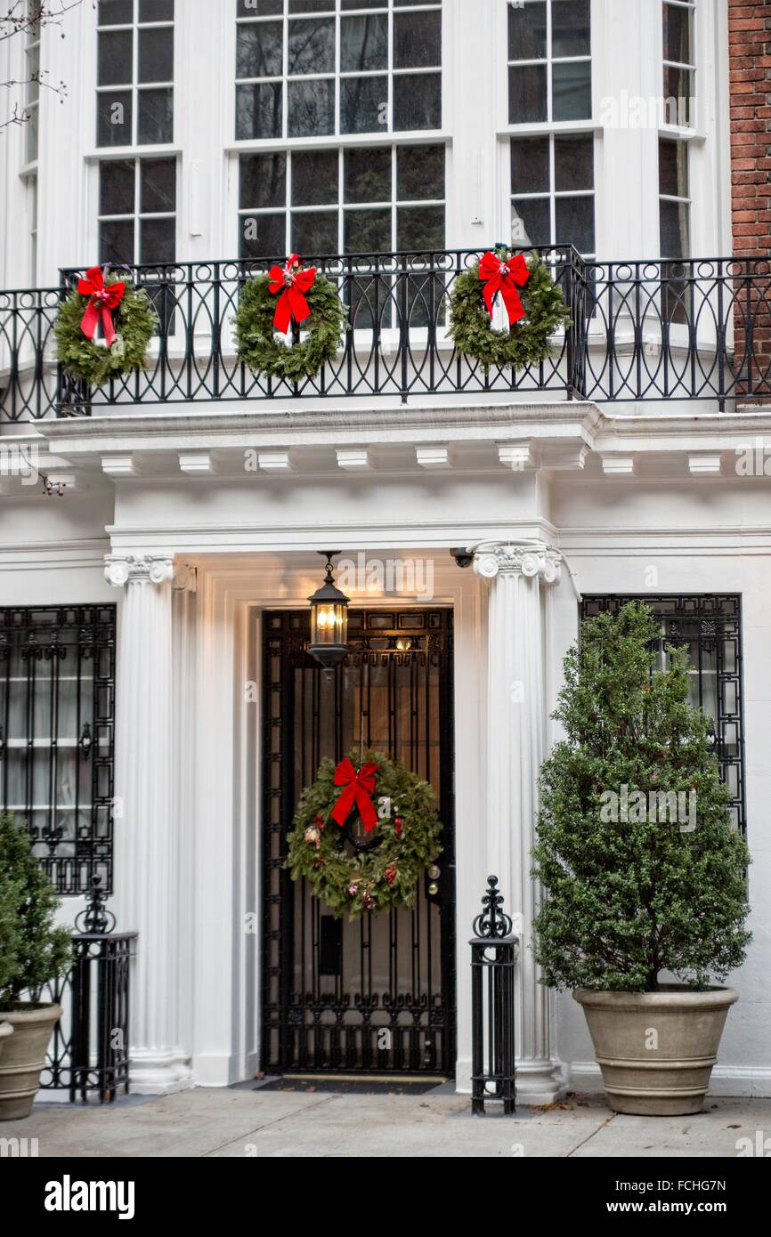 Christmas wreaths decorating the door and balcony of an for When does new york start decorating for christmas