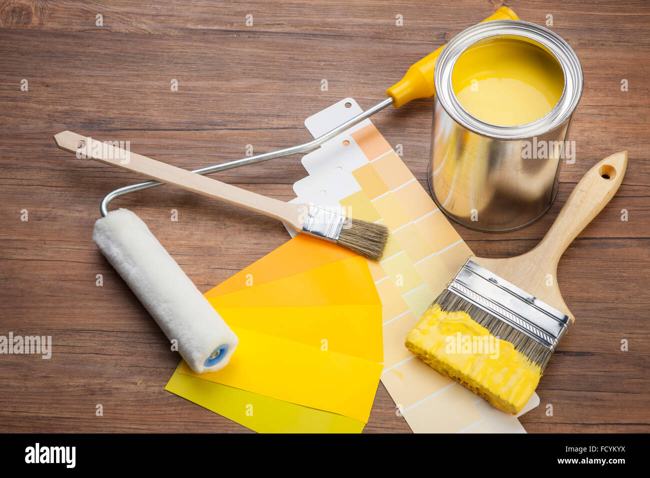 high angle of yellow paint and paint brush dipped in yellow paint